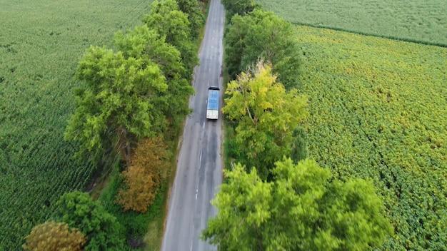 アスファルトで覆われた田舎道でのトラックの動き、車両のドローンによる木々の上空の飛行