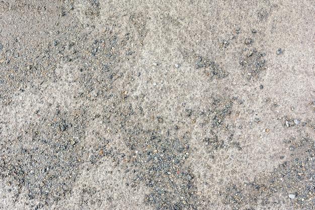 泥だらけのコンクリートの道は細かい砂利のパン粉で覆われています
