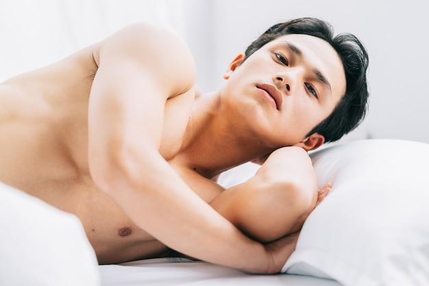 筋肉質の男がベッドに横たわっています