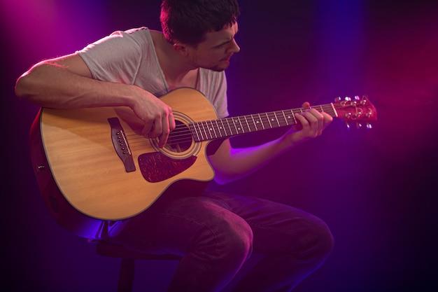 ミュージシャンはアコースティックギターを弾きます。美しい色の光線。