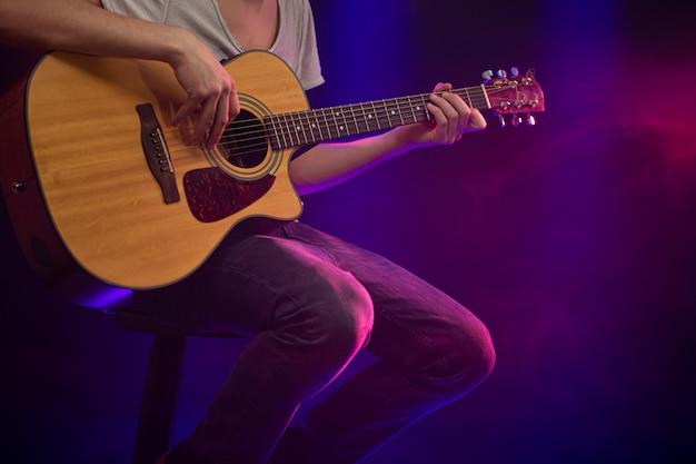 Музыкант играет на акустической гитаре.