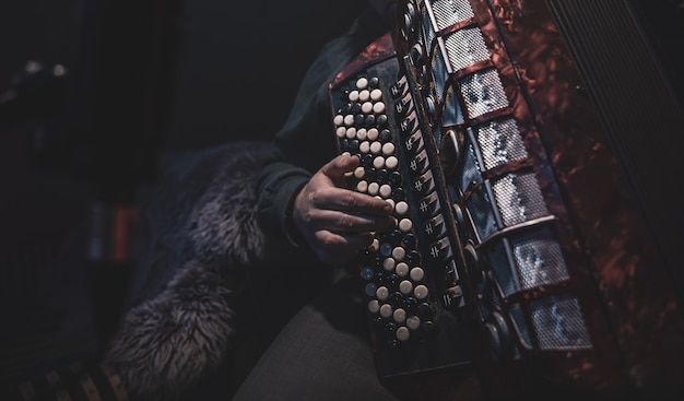 음악가는 스튜디오에서 버튼 아코디언을 연주합니다.