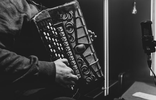 뮤지션은 스튜디오에서 버튼 아코디언을 연주합니다.