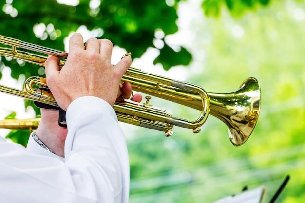 Музыкант играет на трубе во время концерта под открытым небом.