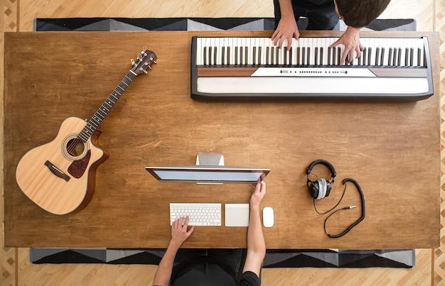 음악가들은 그의 스튜디오에서 키보드를 연주하여 음악을 만듭니다. 소리의 프로세스 녹음.