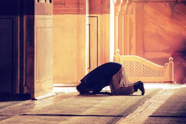 모스크에서 신을 위한 이슬람 기도. 늙은 이란 이슬람교도가 무릎을 꿇고 기도하고 있습니다. 라마단 무슬림의 성월. 이슬람교도, 모하메단, 이슬람교도. 수도사, 수도사, 수도사,