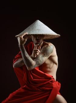 Обнаженный стройный самурай в красном плаще и азиатской шляпе