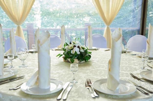 Салфетка красиво сложена на тарелках, обслуживая праздничный банкет.
