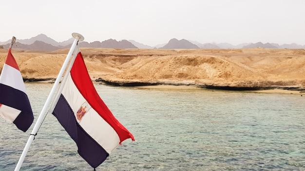 Государственный флаг развевается на ветру на фоне лазурной воды красного моря и каменистого песчаного берега. крупный план. пейзаж красного моря. экскурсия на теплоходе в шарм эль шейх.