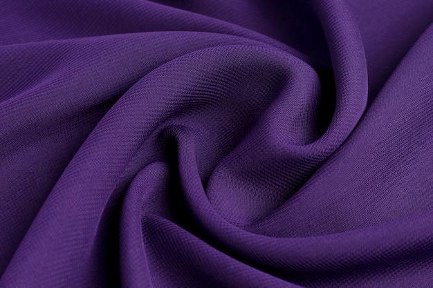 Натуральная хлопчатобумажная ткань фиолетового цвета украшена волнами.