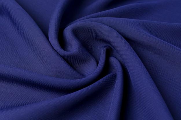 Синий фон с текстурой натуральной хлопковой ткани усеян волнами