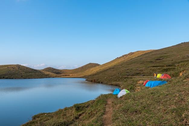 牧草地の自然湖には湖のそばにたくさんのテントがあります