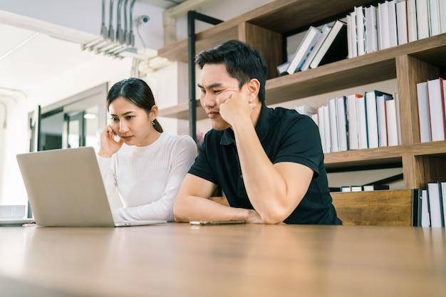긴장된 아시아 인 남성과 여성이 노트북 앞에 앉아 나쁘고 불편한 느낌으로 바라보고 있습니다.