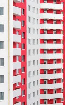 Новый многоэтажный бело-красный жилой дом.