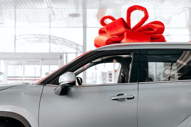 Новую машину окутывают красным бантом. красивая концепция подарка