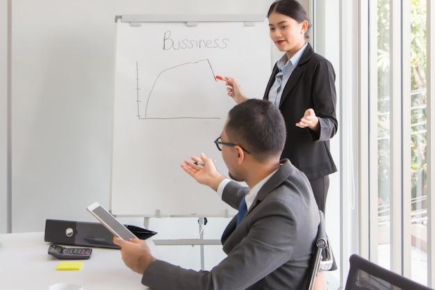 新しい女性会社員は、最新の四半期の結果を午前中に会議室のボスに報告しています。