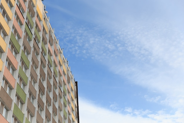 Новый многоэтажный жилой дом на фоне голубого неба.