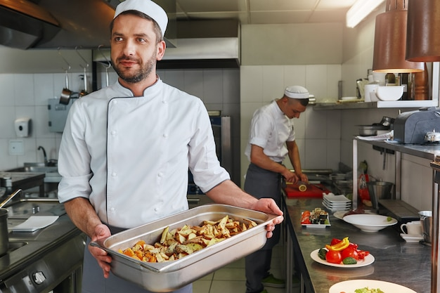 Новая традиция - повар хорошего питания готовит вкусное блюдо на коммерческой кухне.