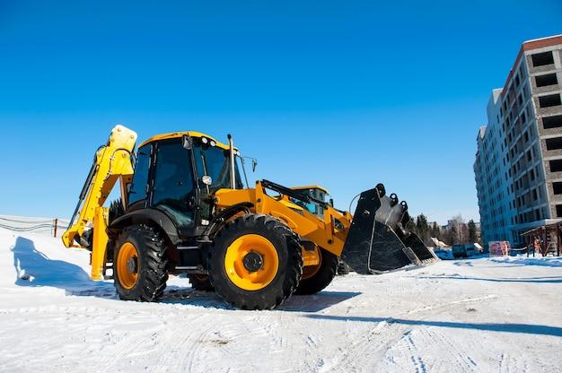 新しい黄色の掘削機は青い空を背景に立っています