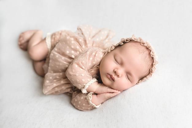 Новорожденный сладко спит, прижав руки к щекам.