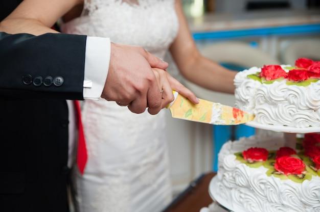На свадьбе молодожены разрезают торт.