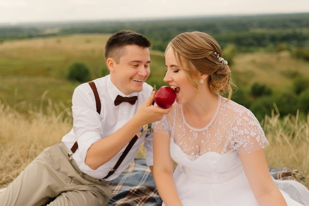 新婚夫婦は自然の中でピクニックをしました。結婚式の後の新郎新婦。
