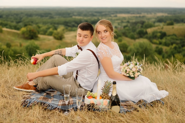 自然の中のピクニックの新婚夫婦。結婚式の後の新郎新婦。