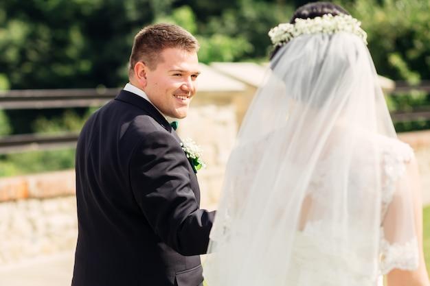 新婚夫婦は手をつないでお互いを見て歩きますエレガントなスーツを着た新郎は花嫁に微笑みかけます
