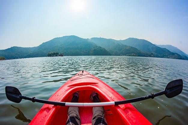 호수 표면 위에 있는 빨간 카약의 코와 카약을 가로질러 누워 있는 노