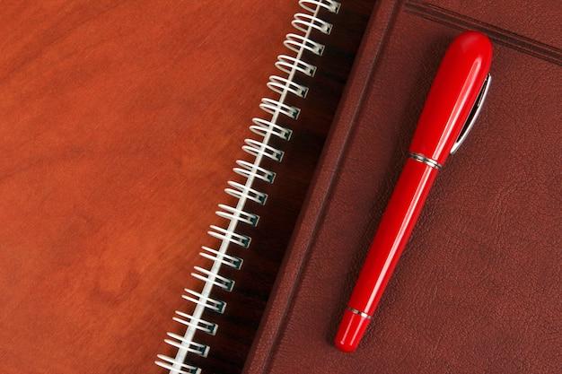 노트북과 나무 책상에 누워있는 빨간 펜