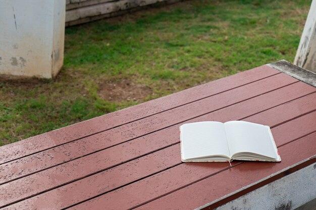 Тетрадь поставили на деревянный стол в саду.