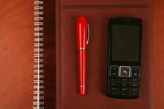Блокнот с красной ручкой и мобильный телефон лежат на столе.