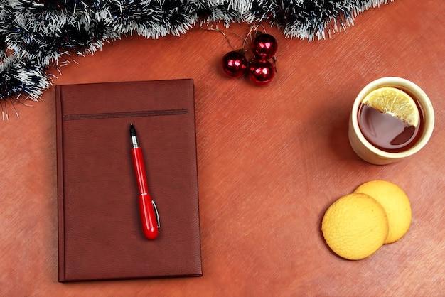 Блокнот с ручкой на офисном столе рождественский чай