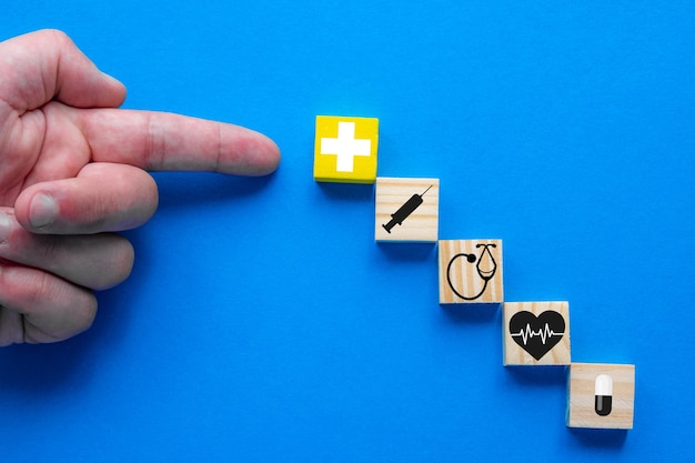 Понятие медицинского страхования. на синем фоне рука указывает на деревянные блоки с медицинскими символами.