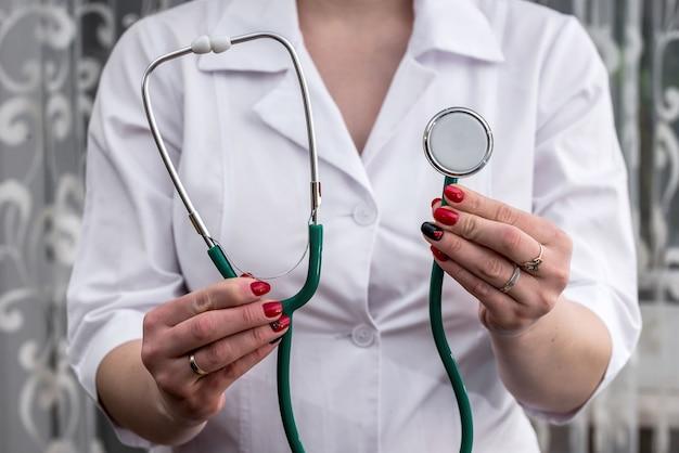 Медсестра держит в руках стетоскоп.