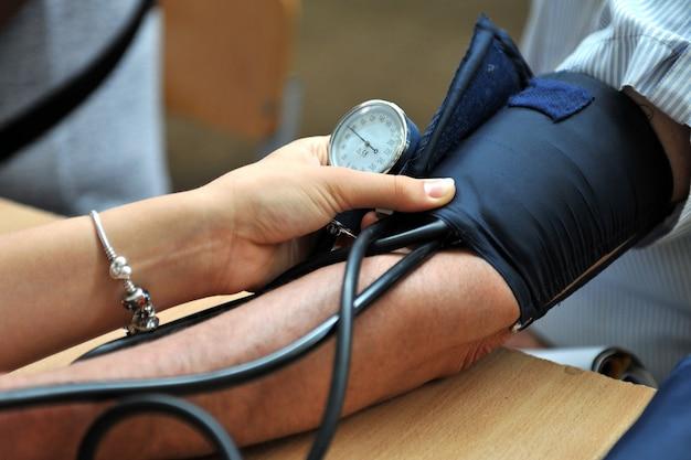 Медсестра измеряет артериальное давление пациента. выборочный фокус