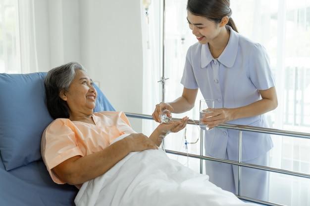 看護師はよくケアされて病院のベッドで高齢の患者に薬を与える患者は幸福を感じる-医療とヘルスケアの上級患者のコンセプト