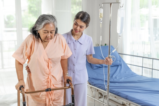看護師は病院のベッドの患者、医療およびヘルスケアの概念で高齢者の患者の世話をします
