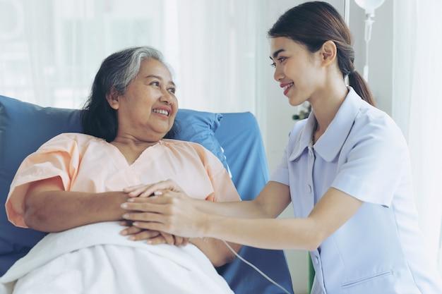 간호사는 병원 침대에서 노인 여성 환자를 잘 돌보는 환자는 행복을 느낍니다-의료 및 건강 관리 개념