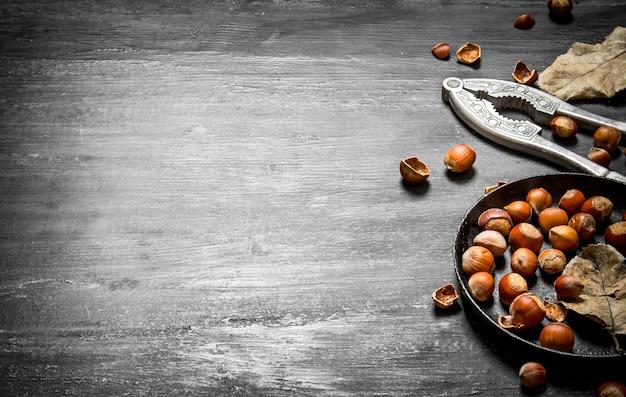 Щелкунчик с фундуком и сушеными листьями на черном деревянном столе