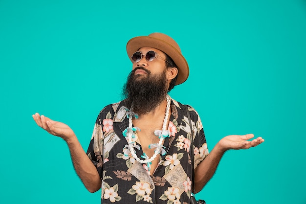 Счастливый человек с длинной бородой в шляпе, в полосатой рубашке, показывающей жест на синем фоне.
