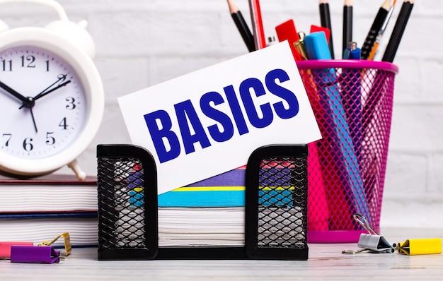オフィスデスクには、日記、目覚まし時計、文房具、basicsというテキストの白いカードがあります。ビジネスコンセプト。