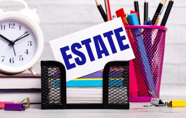 На офисном столе есть дневники, будильник, канцелярские товары и белая карточка с текстом estate. бизнес-концепция.