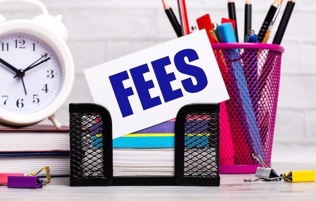 На офисном столе есть дневники, будильник, канцелярские товары и белая карточка с надписью fees. бизнес-концепция.