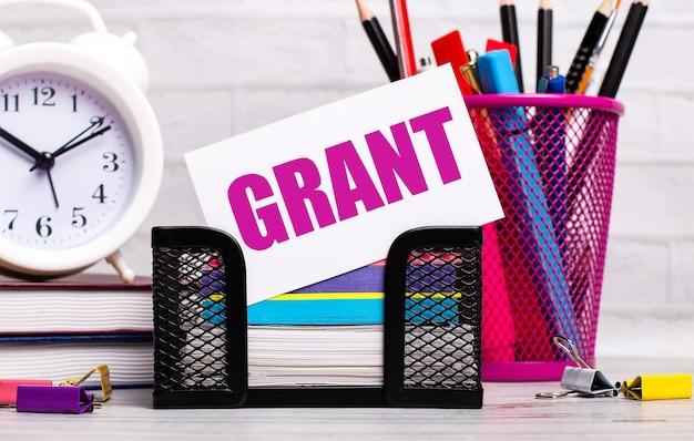 На офисном столе есть дневники, будильник, канцелярские товары и белая карточка с текстом grant. бизнес-концепция.