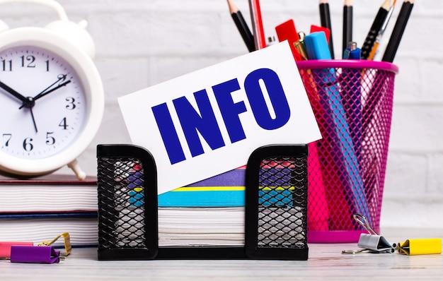 На офисном столе есть дневники, будильник, канцелярские товары и белая карточка с текстом информация. бизнес-концепция.