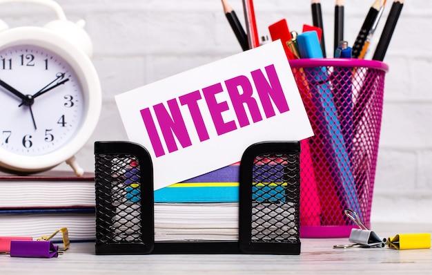На офисном столе есть дневники, будильник, канцелярские товары и белая карточка с текстом intern. бизнес-концепция.