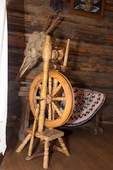 В хижине стоит старая древняя прялка. флис