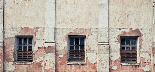壊れたガラスの窓が付いている古くて損傷した放棄された壁