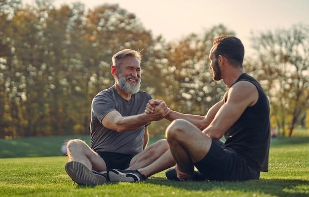 잔디에서 악수하는 노인과 젊은 스포츠맨